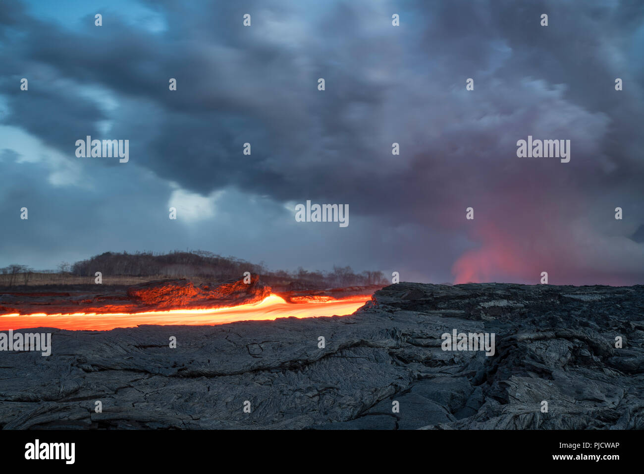 Glowing river of hot lava runs through Kapoho, Hawaii from the Kilauea Volcano east rift zone toward the ocean. Shimmering heat waves distort the view - Stock Image