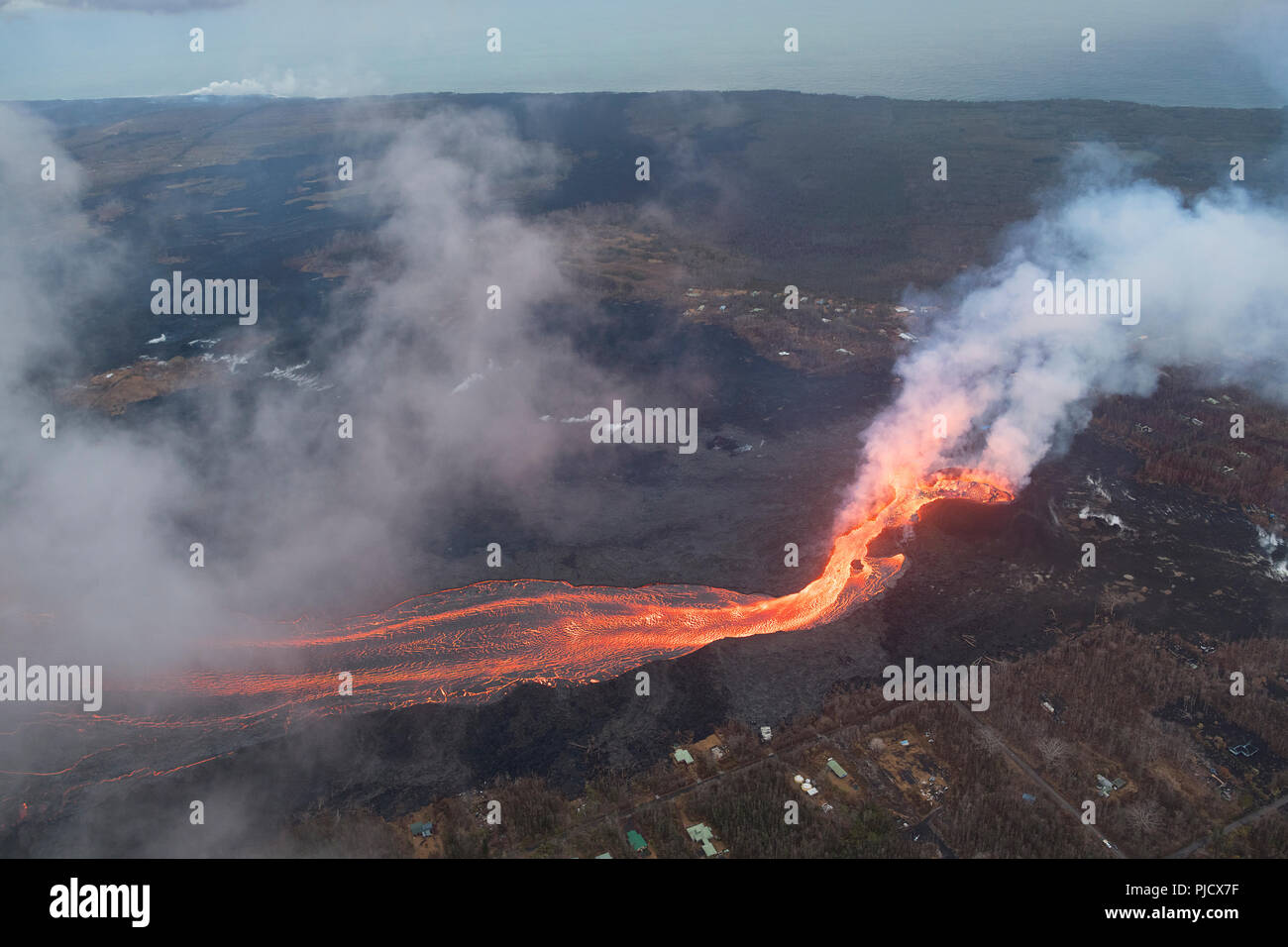 Lava erupts from fissure 8 of the Kilauea Volcano east rift zone in Leilani Estates, near Pahoa, Hawaii, and flows downhill as a glowing river of lava - Stock Image