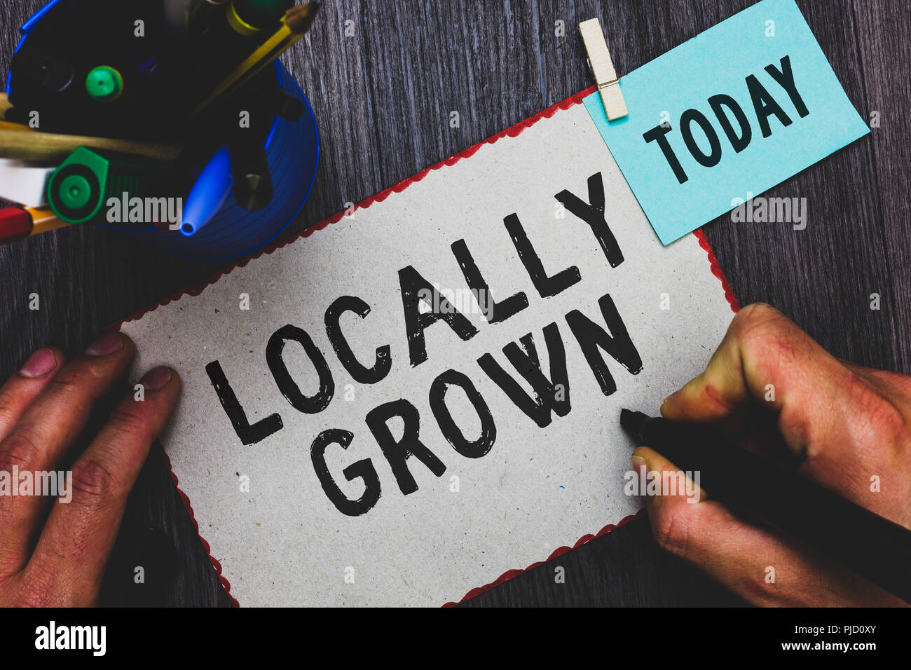 Conceptual hand writing showing Locally Grown. Business photo text Produced Agricultural Countryside Fresh Vegetables Man holding marker paper clothes - Stock Image