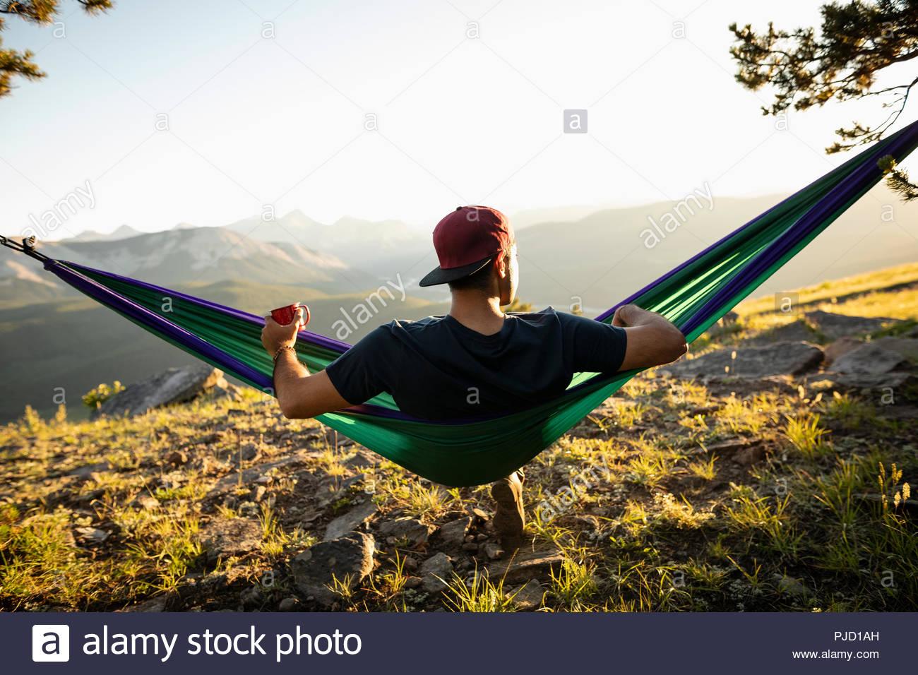 Serene man drinking coffee in sunny hammock with idyllic mountain view, Alberta, Canada - Stock Image