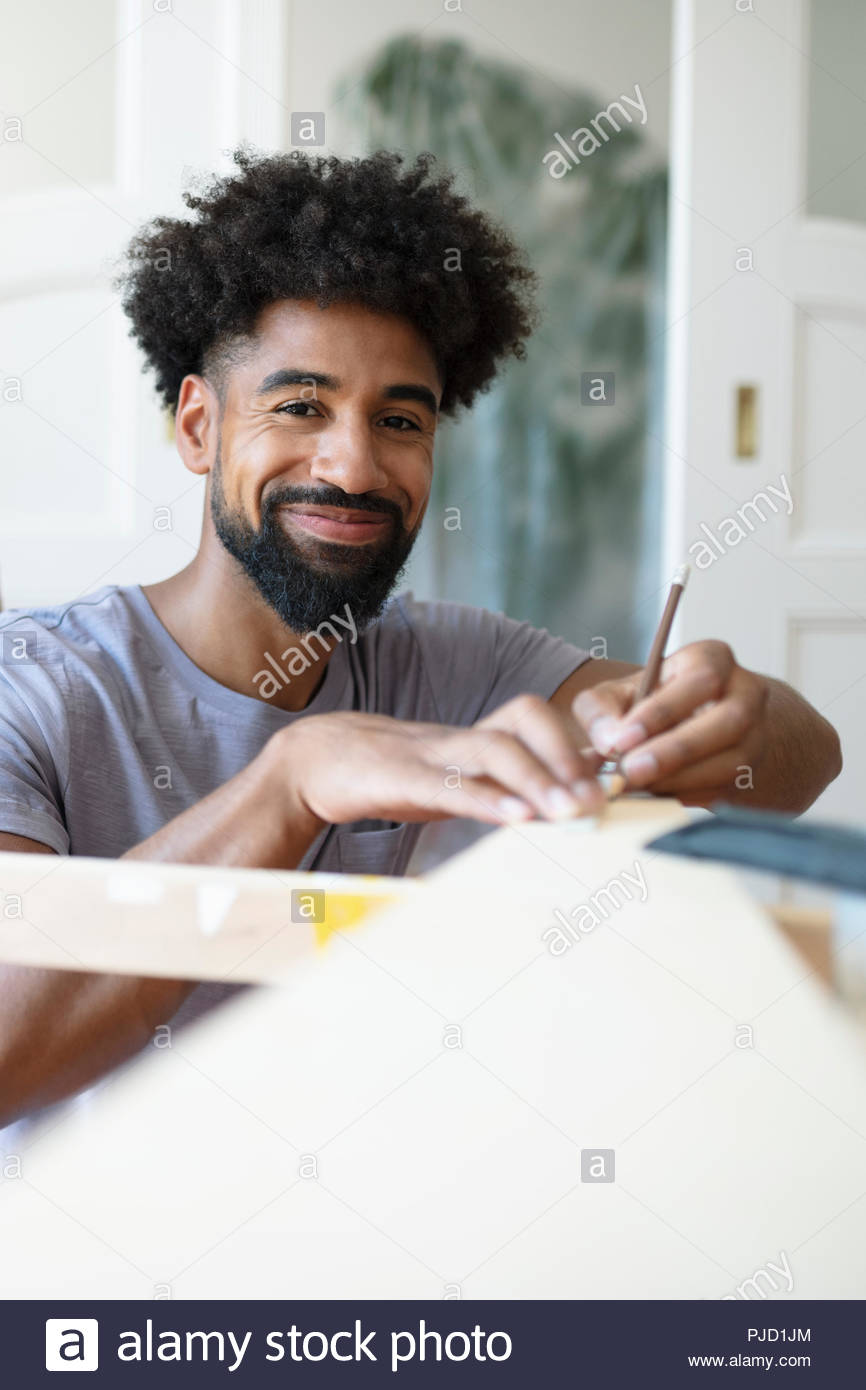 Portrait smiling man doing DIY carpentry project - Stock Image