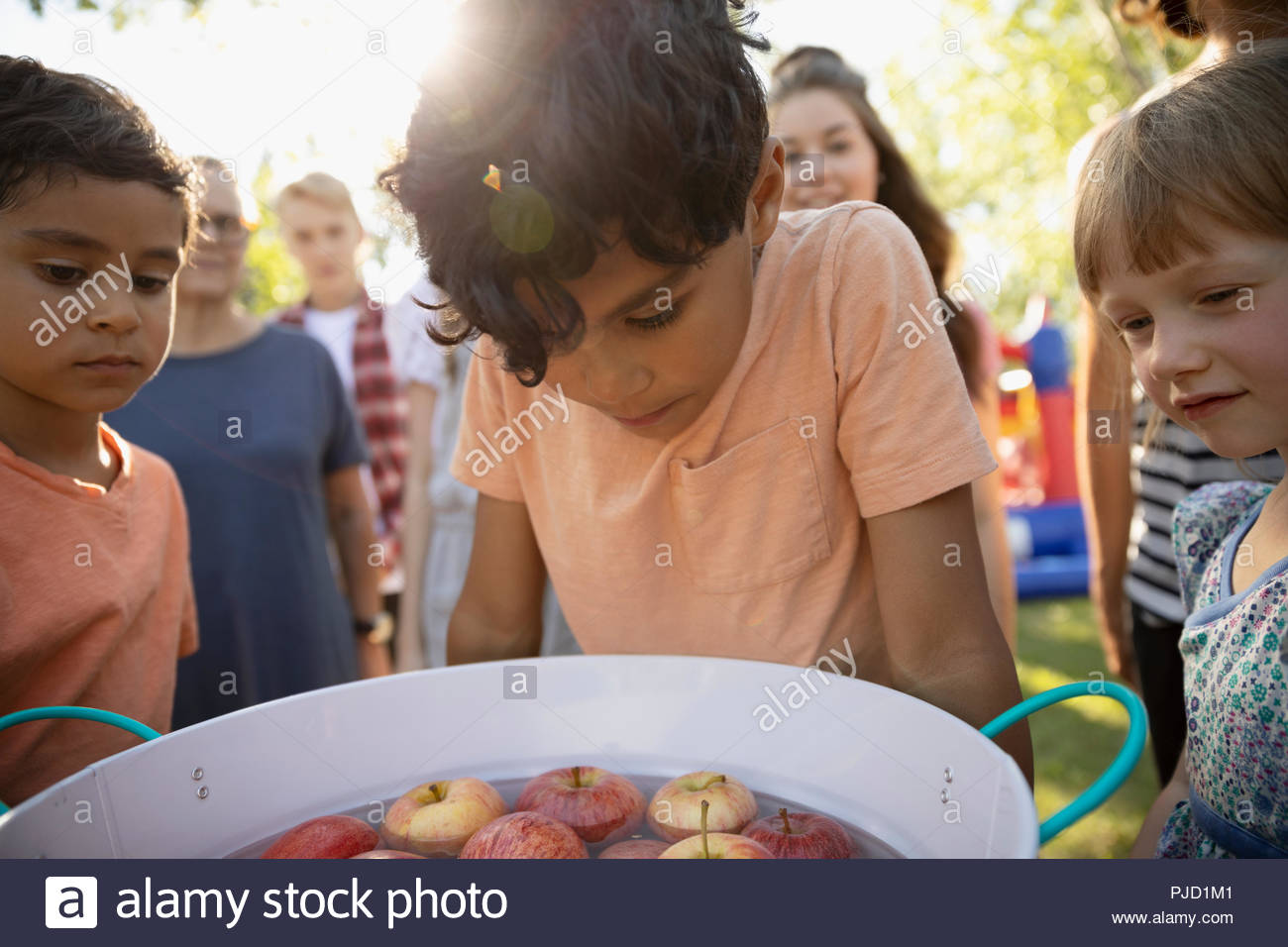 Kids bobbing for apples at summer neighborhood block party in park - Stock Image