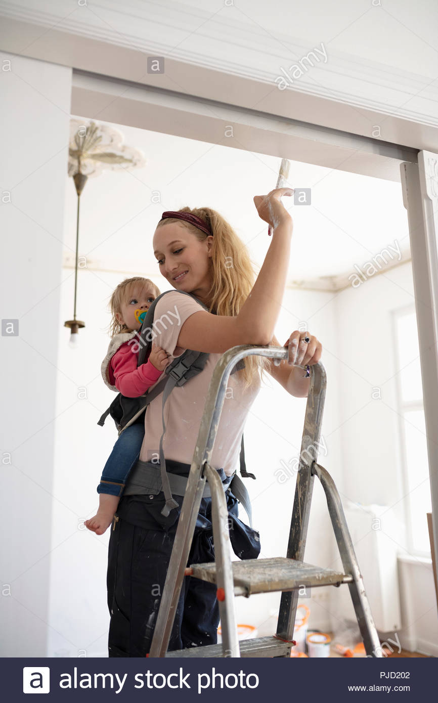 DIY mother painting trim with baby daughter in baby carrier - Stock Image