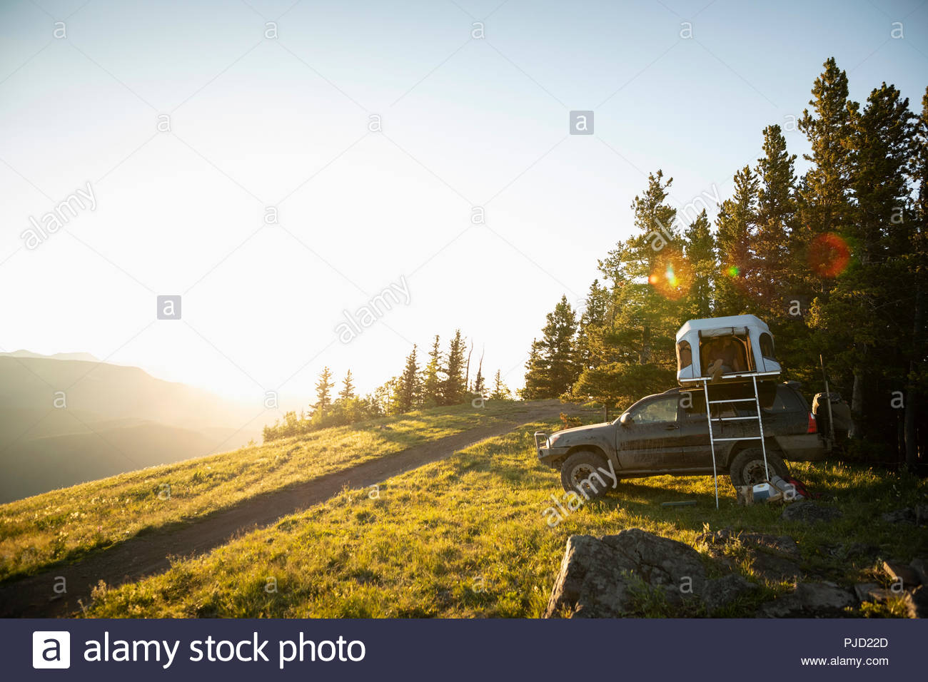 SUV with rooftop tent on sunny, idyllic mountain hilltop, Alberta, Canada - Stock Image