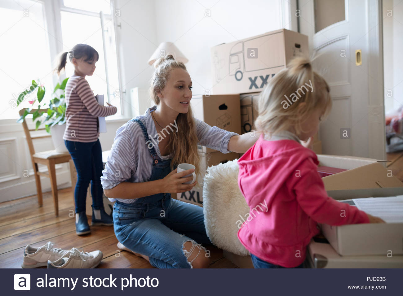 Mother and daughters packing moving boxes - Stock Image