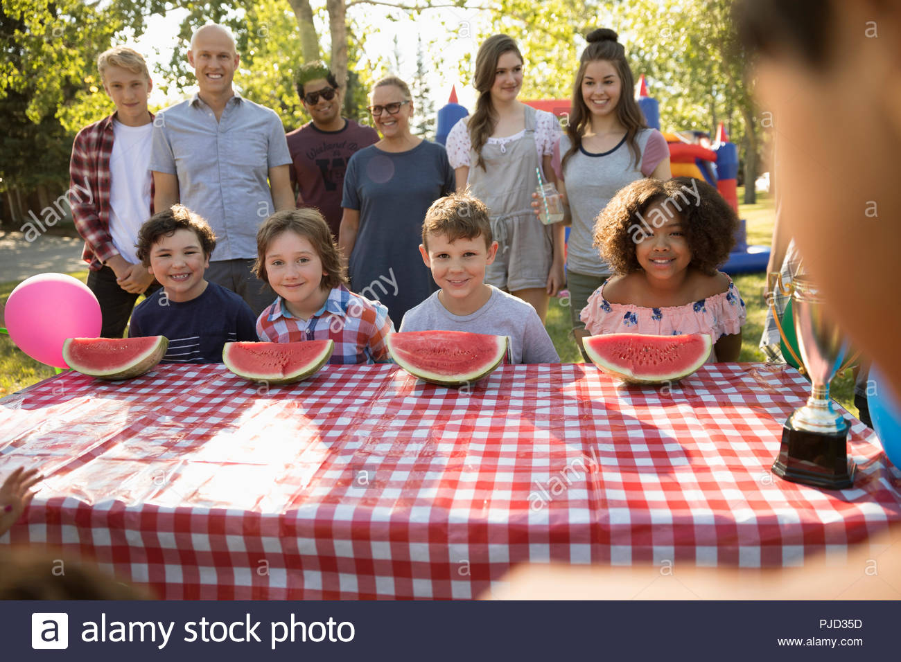 Kids preparing for watermelon eating contest at summer neighborhood block party in park - Stock Image