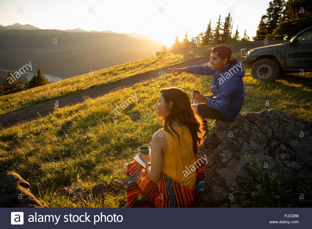 Couple drinking coffee on sunny, idyllic mountain hillside, Alberta, Canada - Stock Image