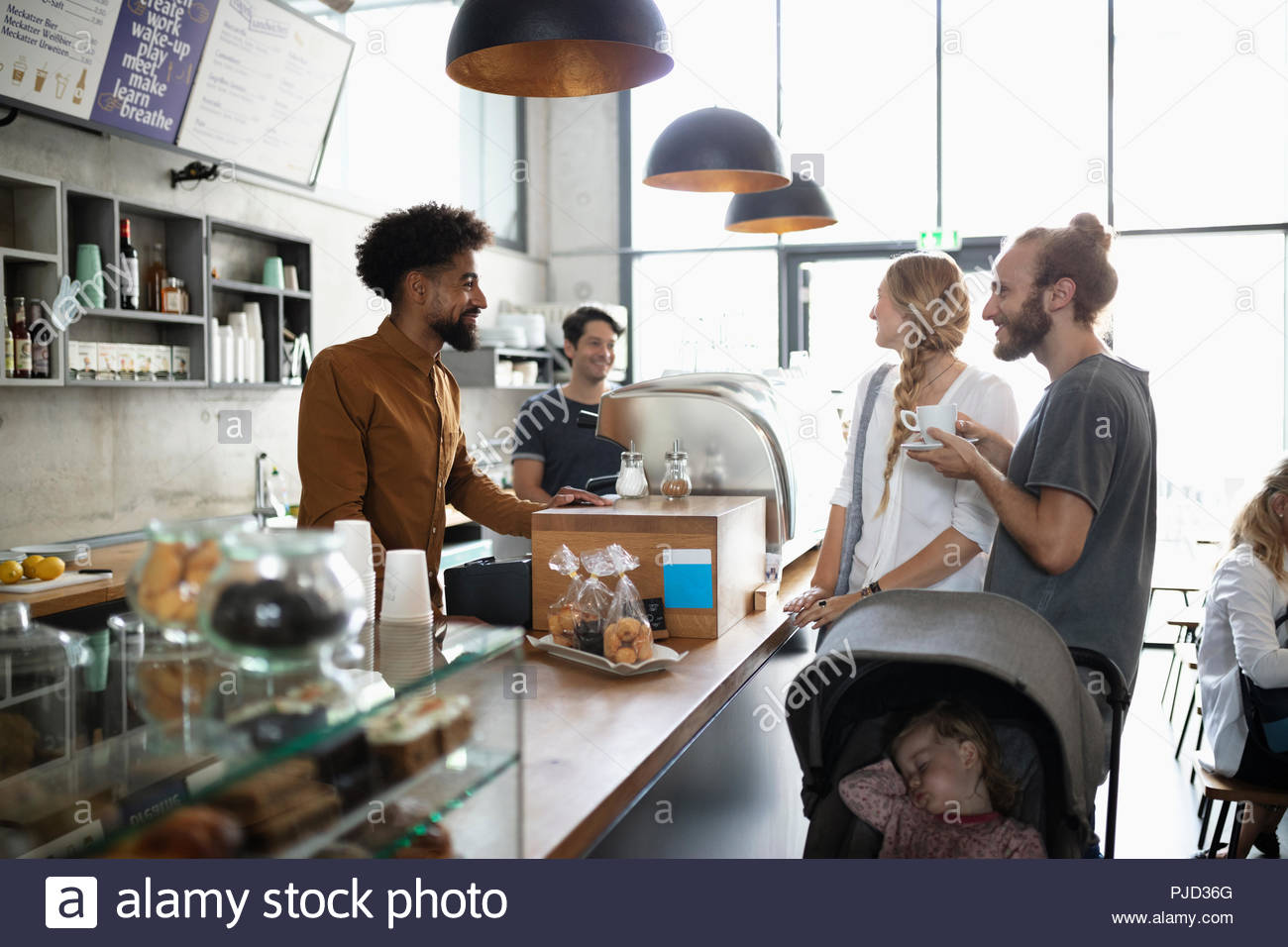 Young family talking with barista in cafe - Stock Image