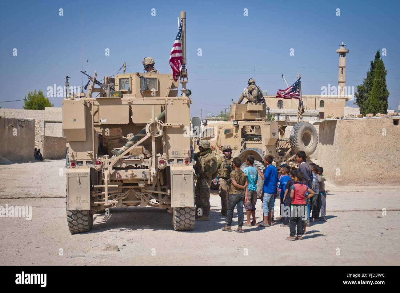 A Group Of Children Gather Around A U S Military Convoy Conducting