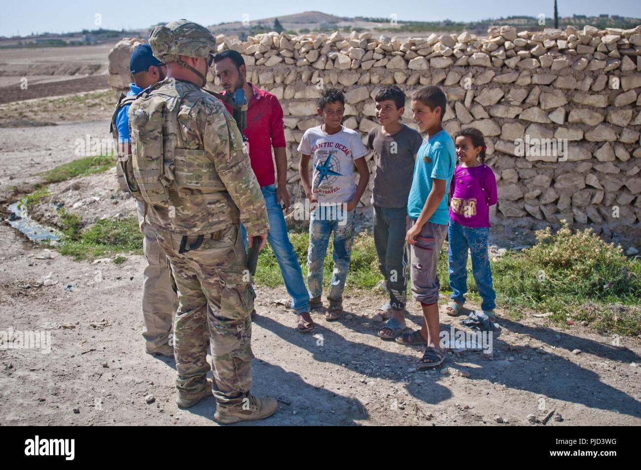 A U S Soldier Talks With Locals While Patrolling Through A Village