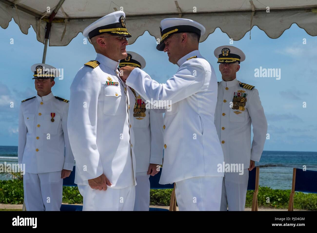 ASAN BEACH, Guam (July 19, 2018) Rear Adm. Troy McClelland, Deputy Commander for the Naval Construction Force, Navy Expeditionary Command, presents Capt. Jeffrey Kilian with a Legion of Merit for his accomplishments as commodore of the 30th Naval Construction Regiment during the regiment's change of command ceremony at the War in the Pacific National Historical Park Asan Beach Unit. During the ceremony, Capt. Steven Stasick relieved Kilian as commodore of 30 NCR. Stock Photo