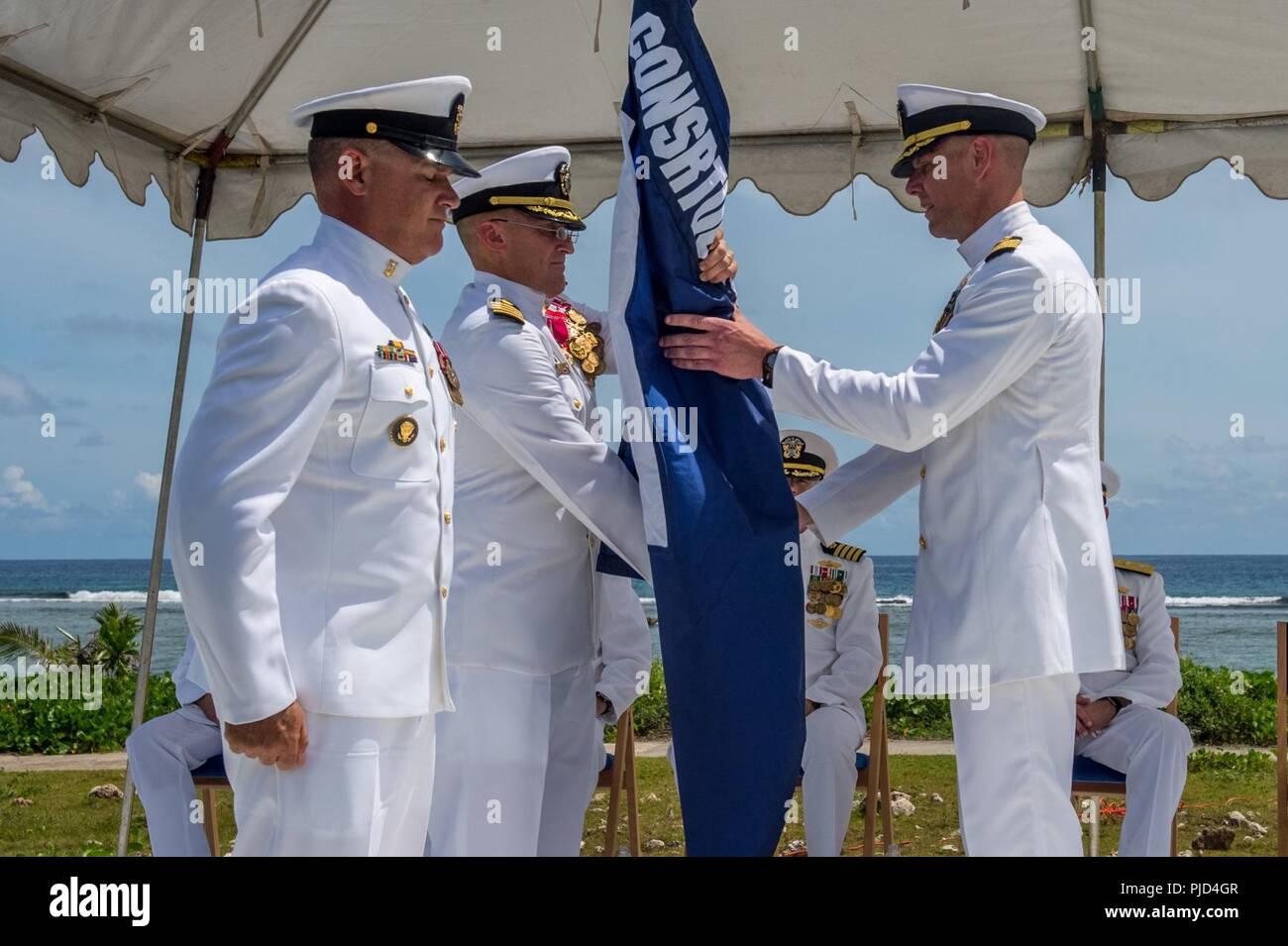 ASAN BEACH, Guam (July 19, 2018) As Command Master Chief Joe Arnold looks on, Capt. Jeffrey Kilian (left) passes the regimental flag to Capt. Steven Stasick during 30th Naval Construction Regiment's (30 NCR) change of command ceremony at the War in the Pacific National Historical Park Asan Beach Unit. The passing of colors from an outgoing commanding officer to an incoming one ensures the unit and its Sailors are never without leadership. Stack relived Kilian during the ceremony. Stock Photo