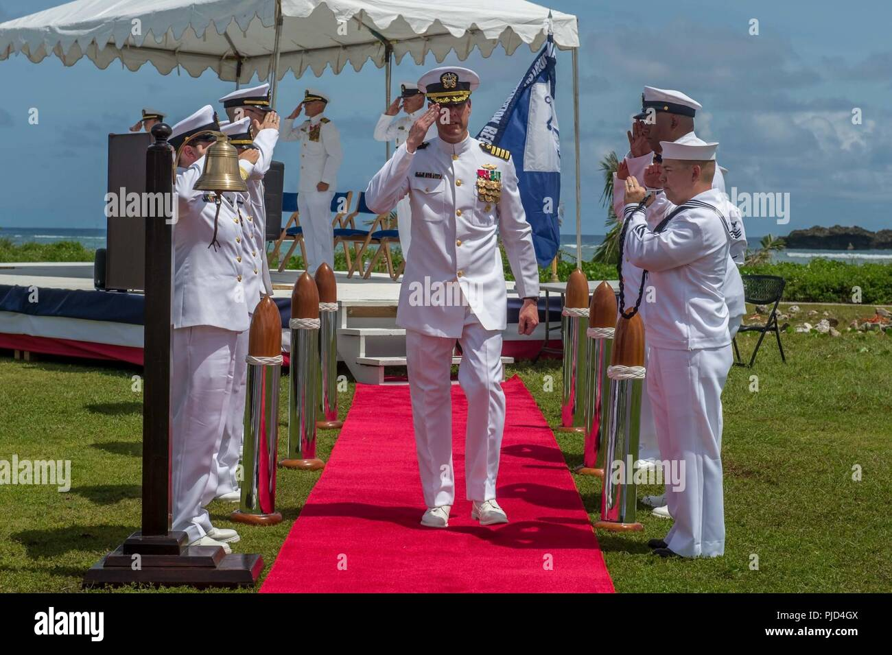 ASAN BEACH, Guam (July 19, 2018) Capt. Steven Stasick, commodore of the 30th Naval Construction Regiment, salutes sideboys following 30 NCR's change of command ceremony. Stack relived Capt. Jeffrey Kilian during the ceremony at the War in the Pacific National Historical Park Asan Beach Unit. - Stock Image