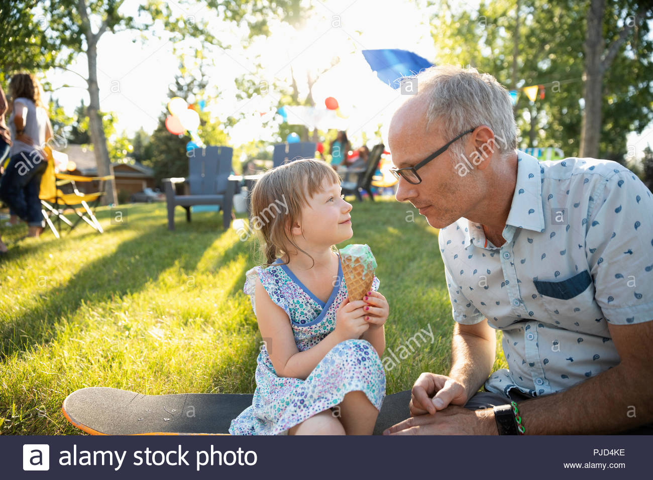 Father and daughter with ice cream cone at summer neighborhood block party in park - Stock Image