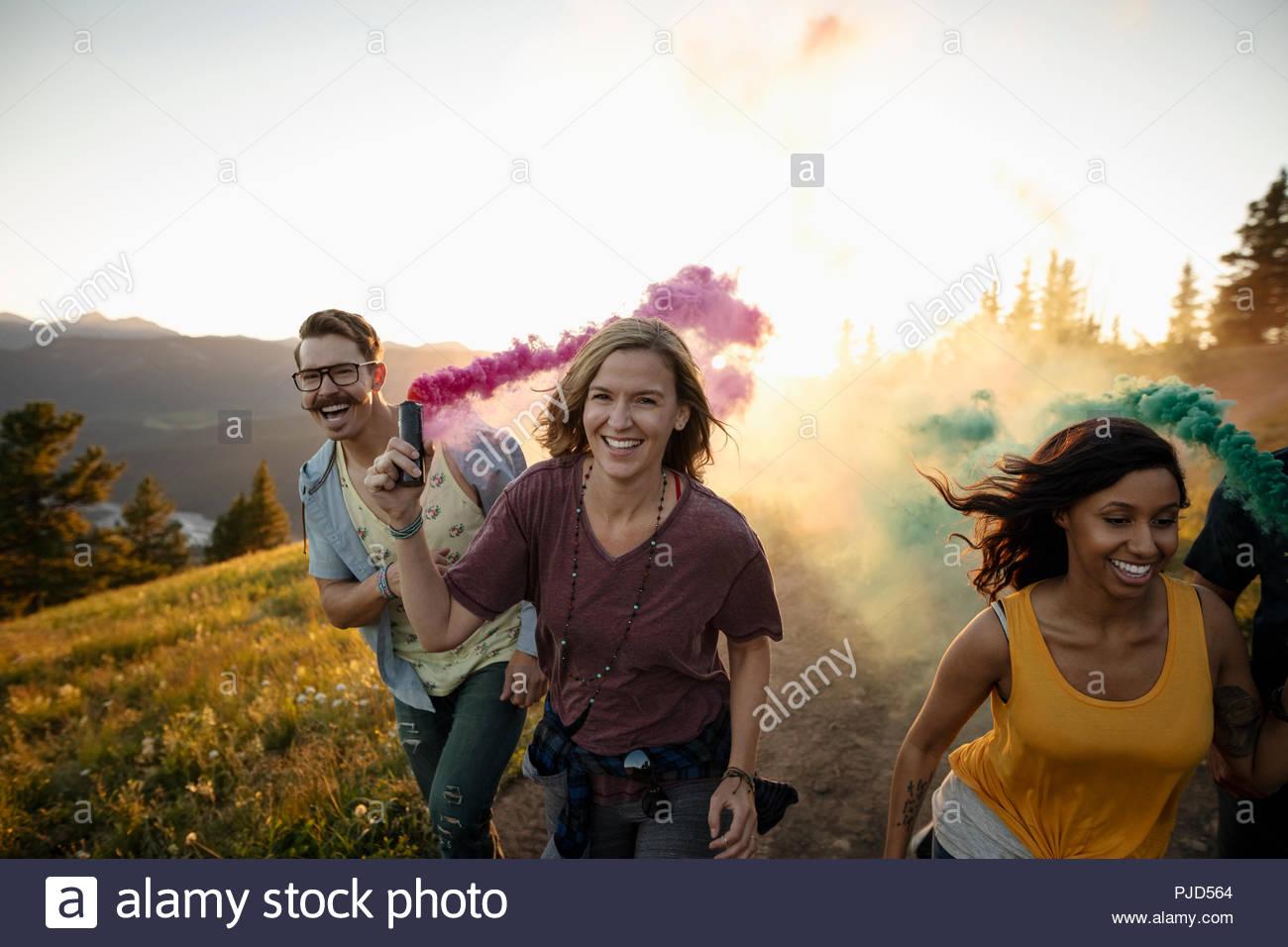 Playful friends enjoying colorful smoke bombs on sunny mountain road - Stock Image