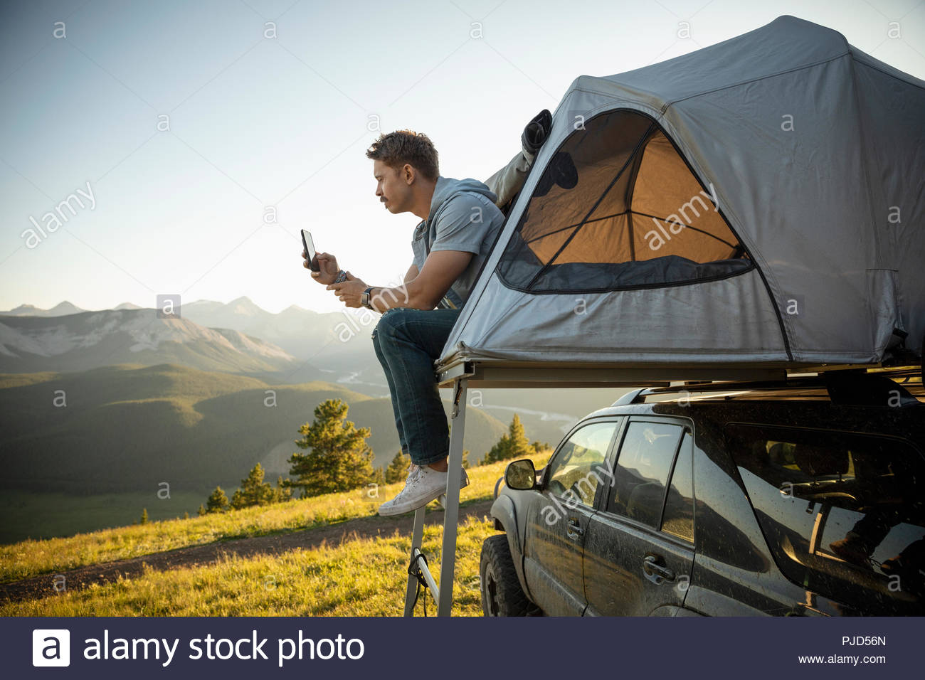 Serene man camping, relaxing at SUV rooftop tent in sunny, idyllic field, Alberta, Canada - Stock Image