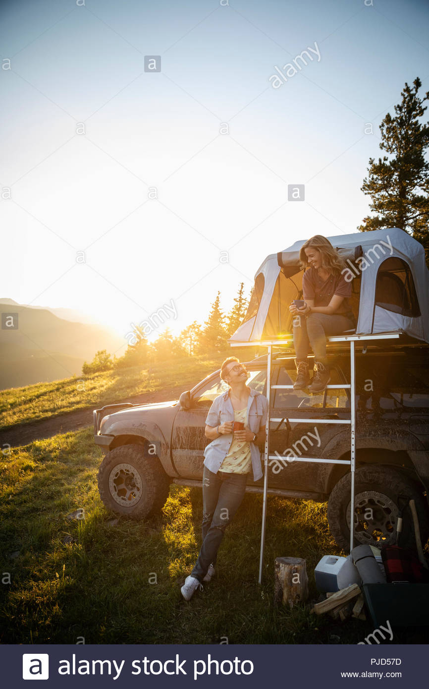 Couple camping, relaxing at SUV rooftop tent in sunny, idyllic field, Alberta, Canada - Stock Image