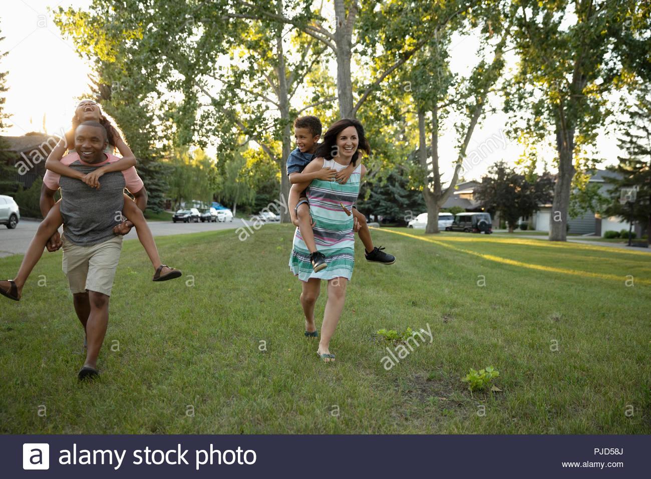 Playful parents piggybacking kids in park - Stock Image