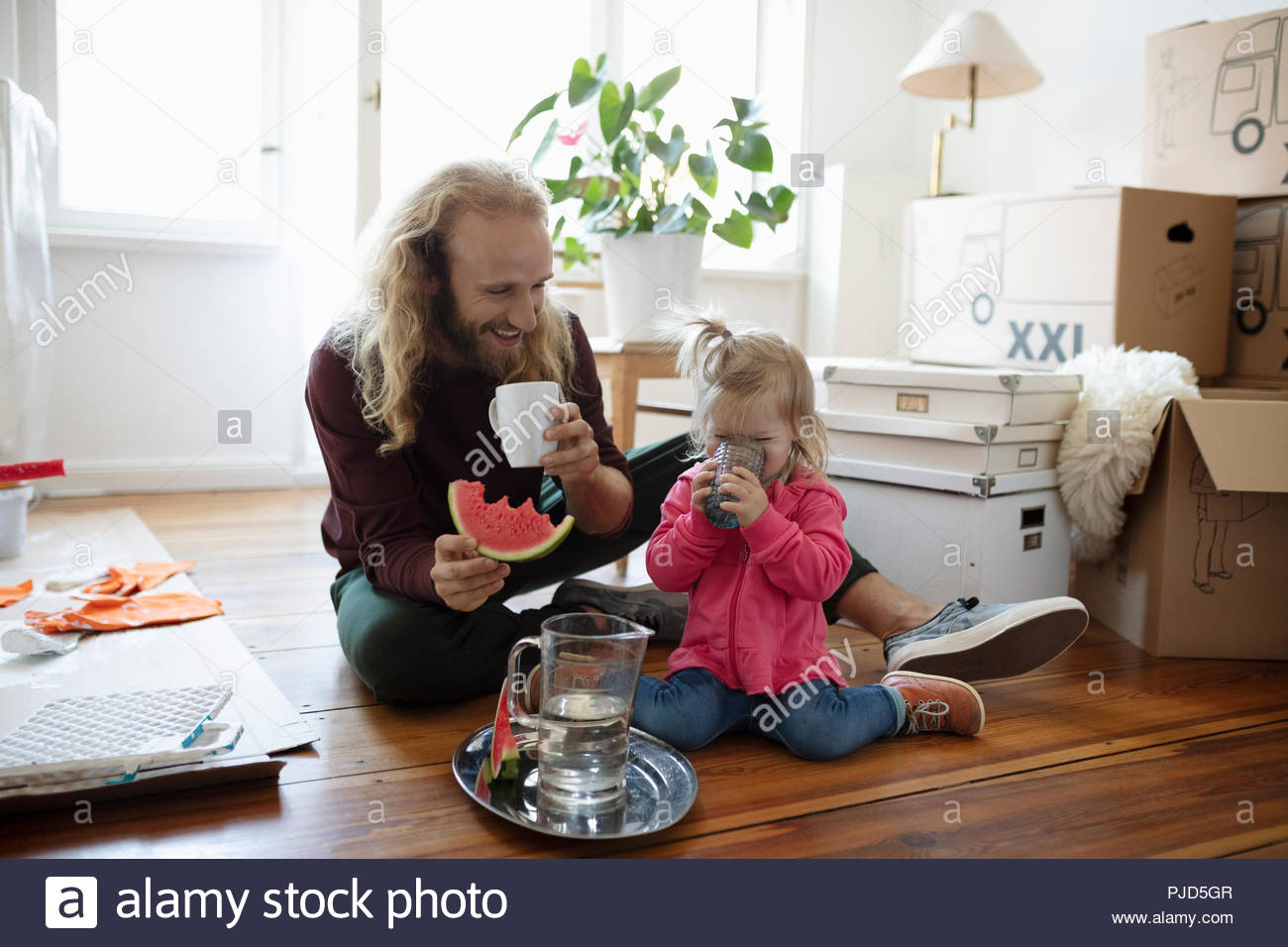 Father and daughter eating watermelon and drinking water, taking a break from moving and painting - Stock Image