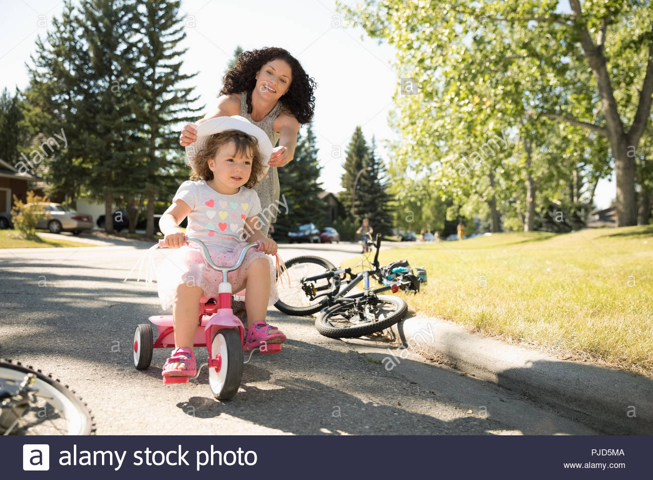 67b9fc6e500 Mother with toddler daughter on bicycle on sunny summer street - Stock Image