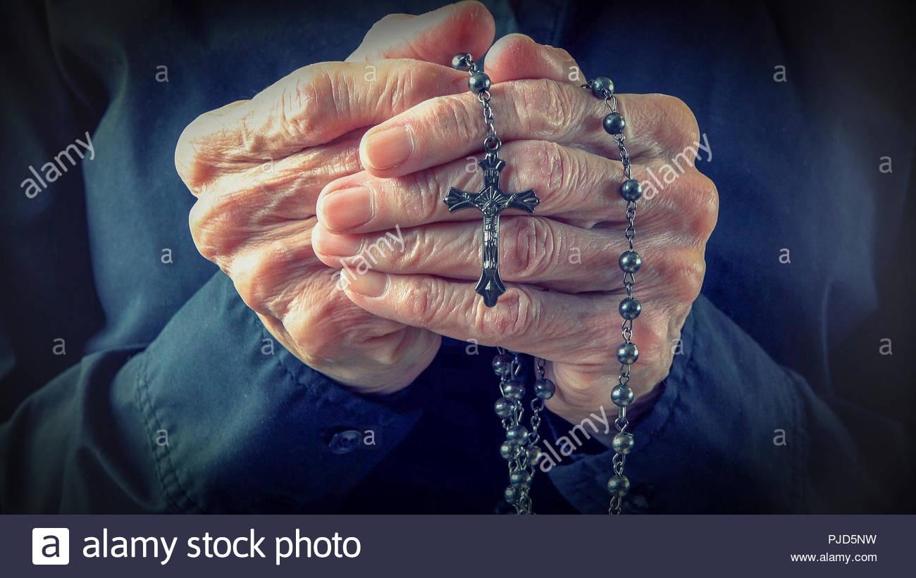 Hands of an elder woman holding a rosary while praying,Christian daily devotional of a worshiper, relationship with God the Creator and Savior - Stock Image