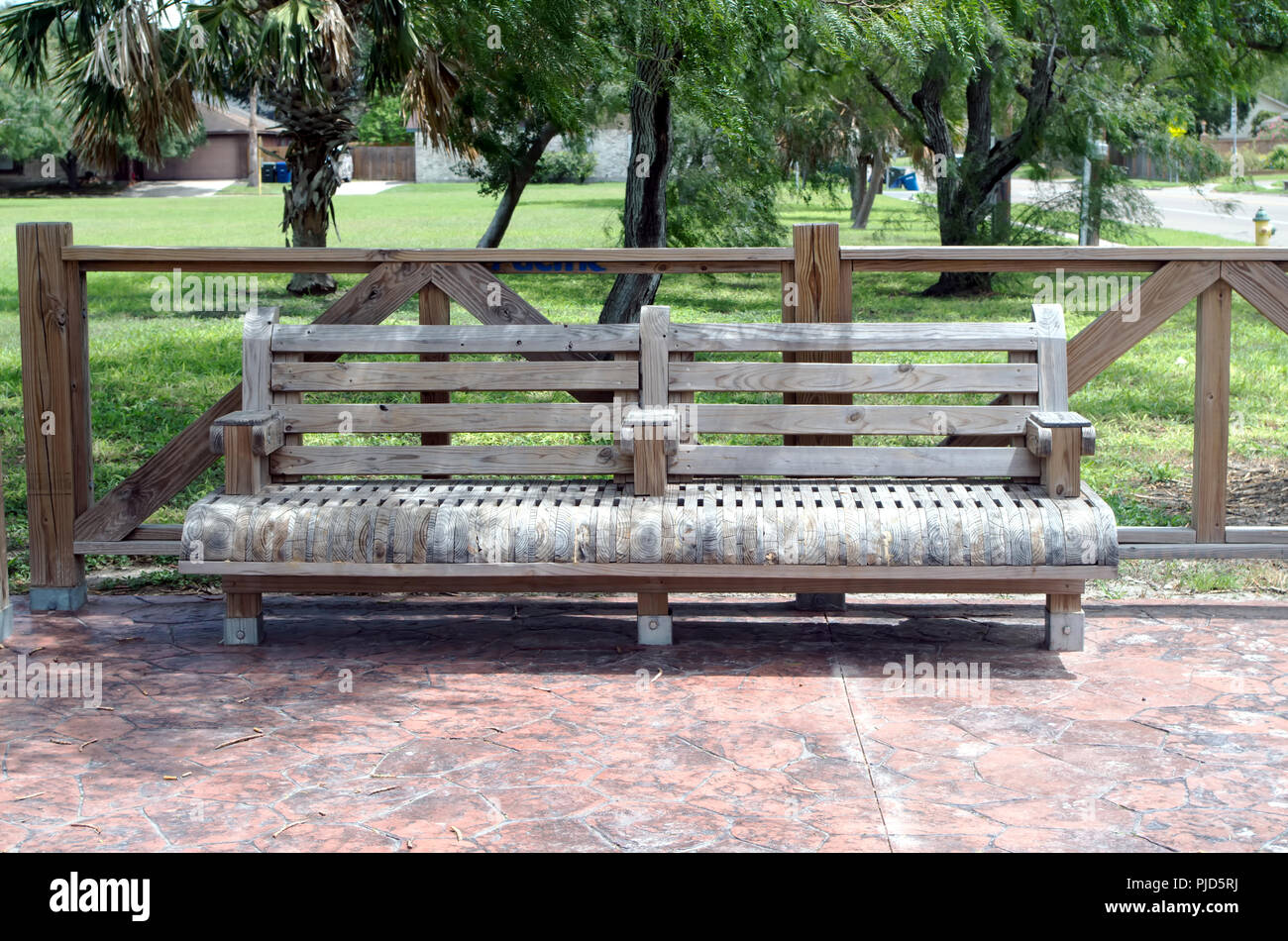 A sturdy wooden bench of unusual style is permanently affixed to stamped concrete (view 2.) Schanen hike and bike trail Corpus Christi, Texas USA. - Stock Image
