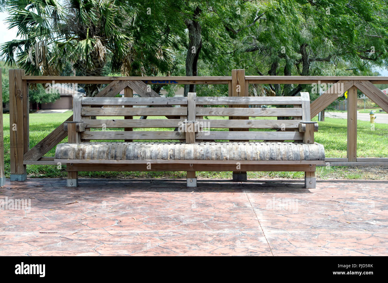 A sturdy wooden bench of unusual style is permanently affixed to stamped concrete (view 1.)  Schanen hike and bike trail Corpus Christi, Texas USA. - Stock Image