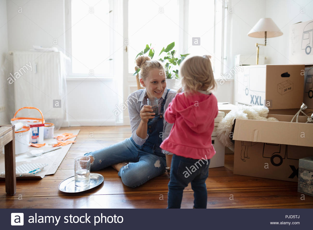 Mother and daughter taking a break from moving in and painting - Stock Image