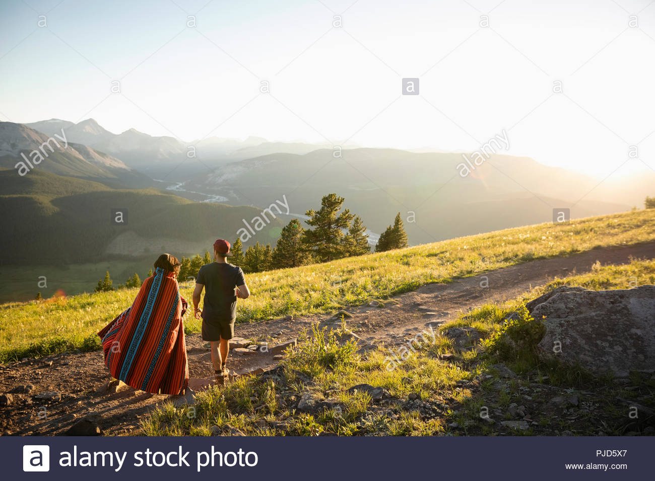 Couple wrapped in blanket walking on sunny mountain hilltop, Alberta, Canada - Stock Image