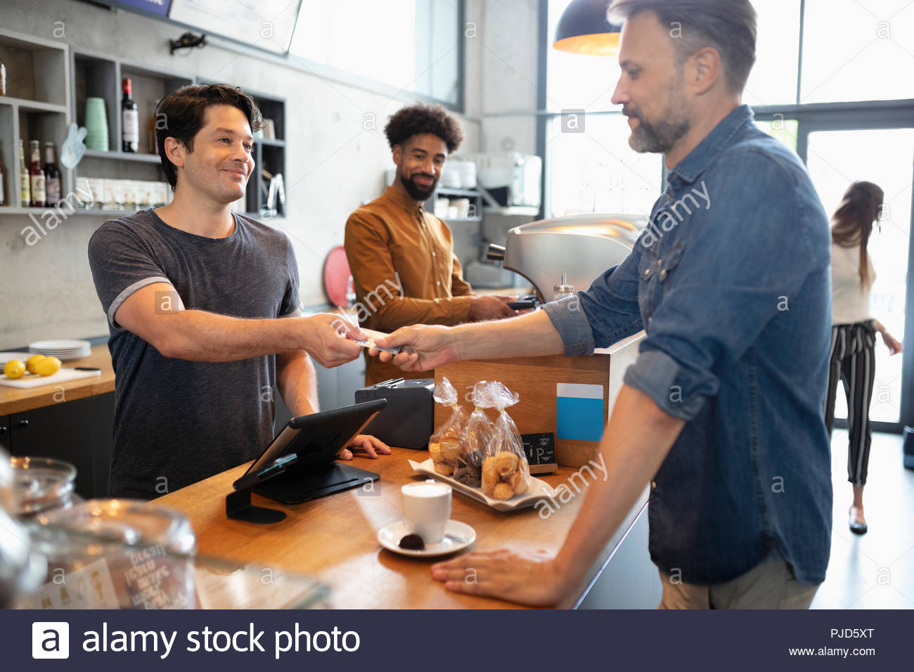 Customer paying for coffee in cafe - Stock Image