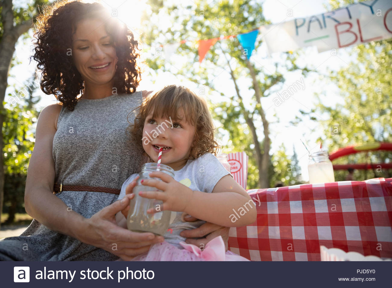 Mother and daughter drinking lemonade at summer neighborhood block party - Stock Image