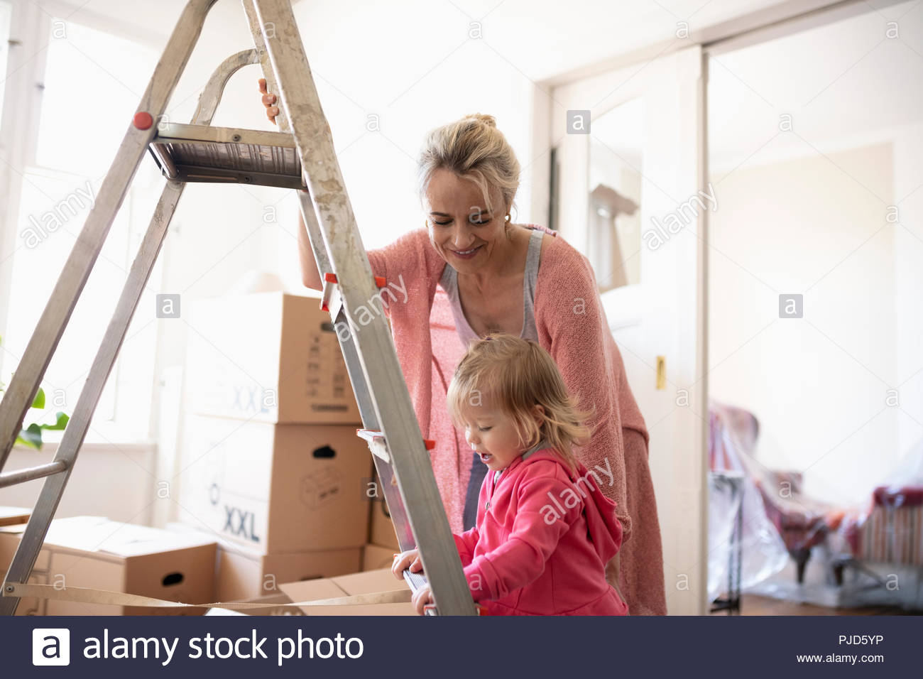 Mother and daughter at ladder, moving into new home - Stock Image