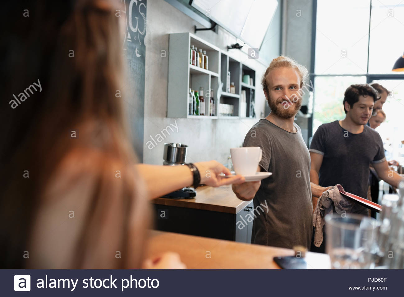 Barista serving coffee to customer in cafe - Stock Image