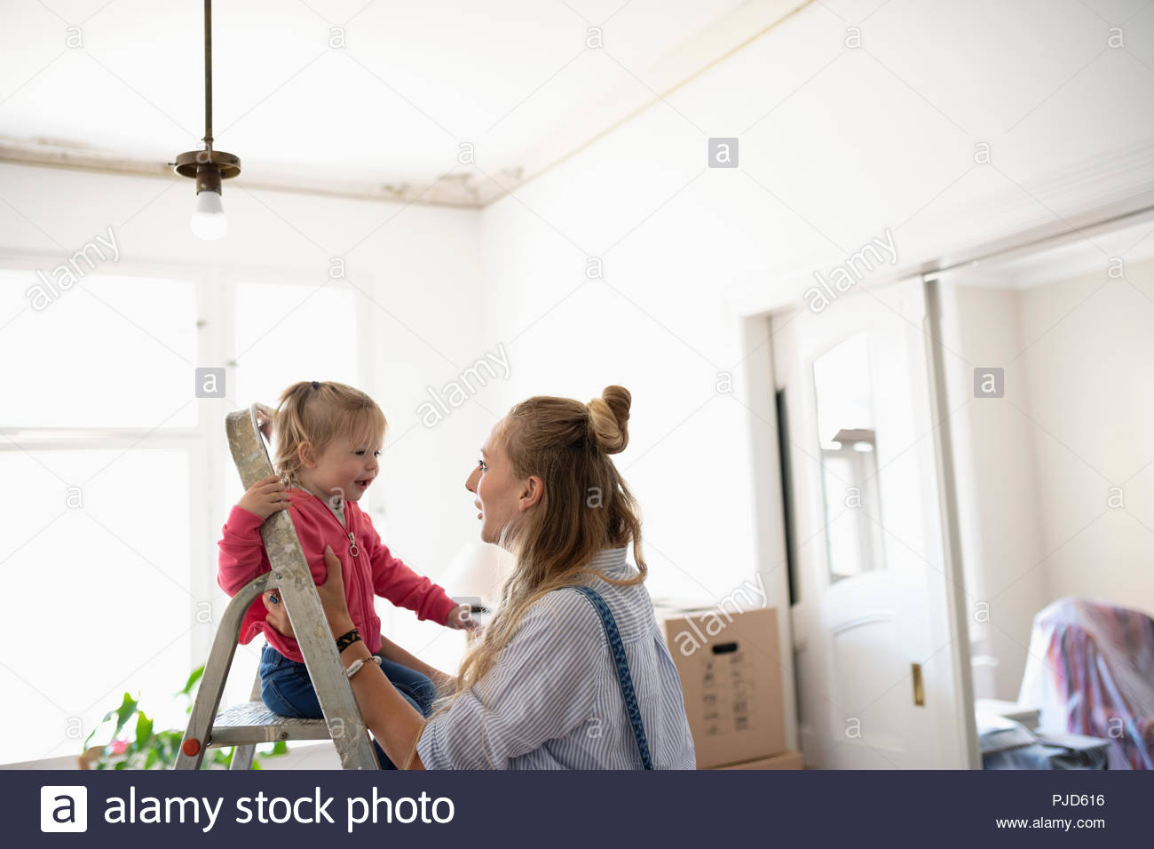 Playful mother and daughter moving into new home - Stock Image
