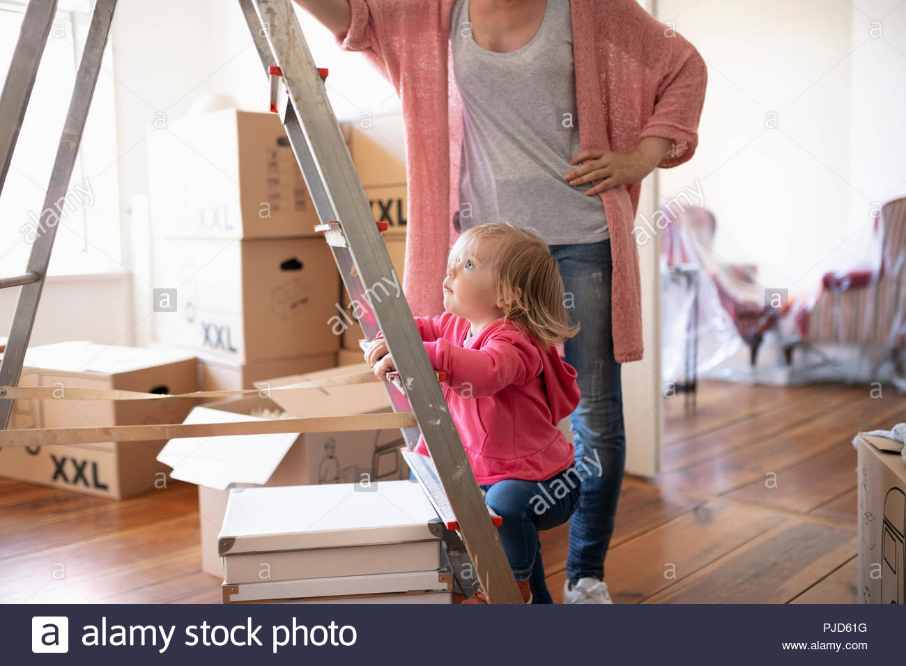 Curious girl climbing ladder, moving into new home - Stock Image