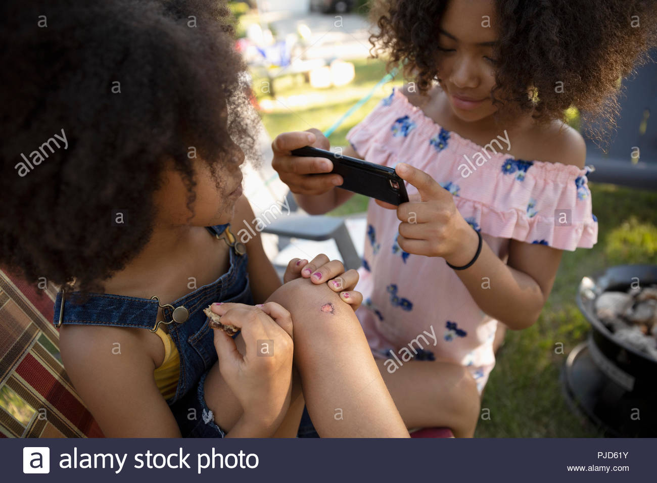 Girl with camera phone photographing sister with scraped knee Stock Photo