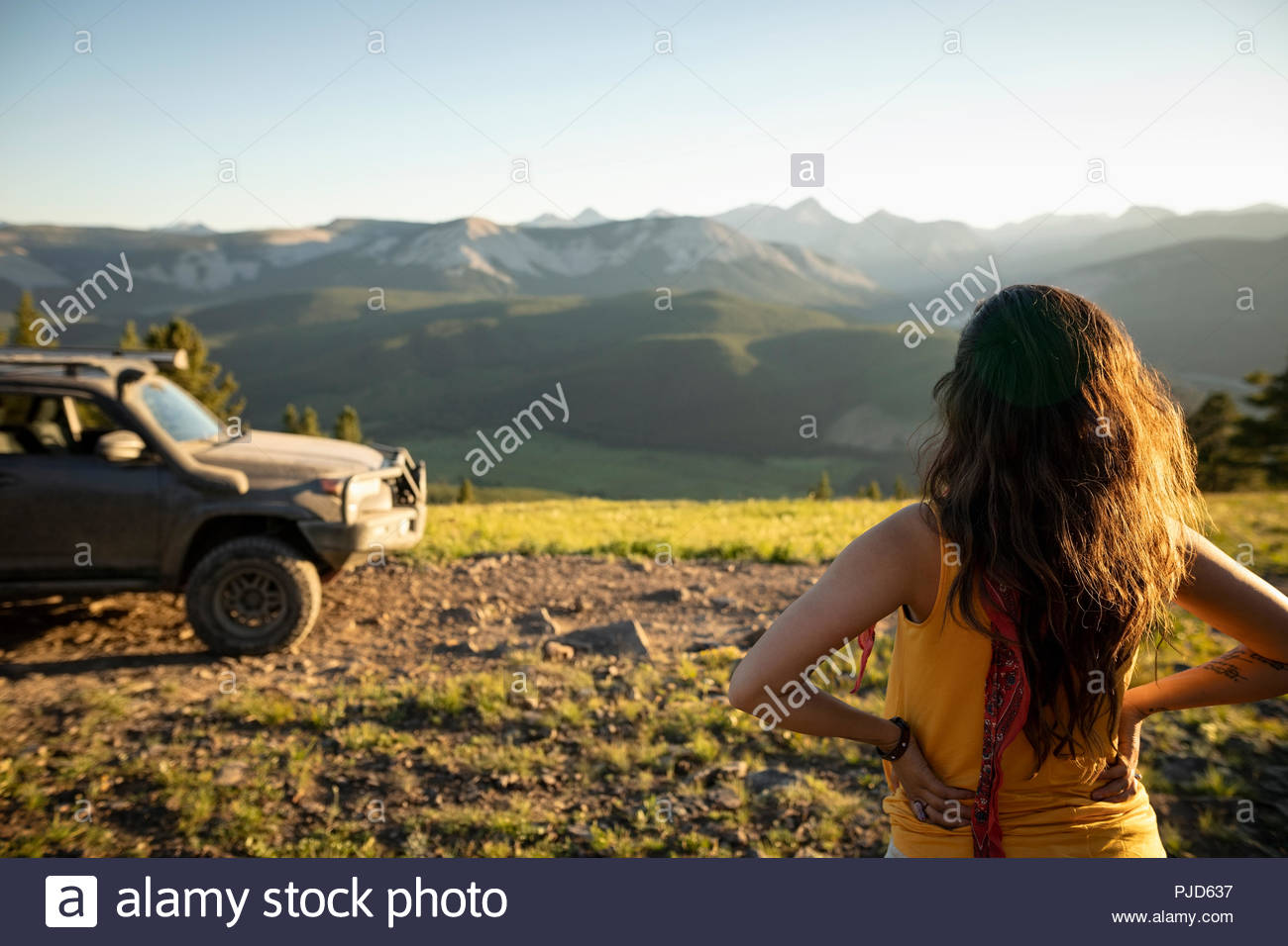 Woman looking at sunny mountain view near SUV, Alberta, Canada - Stock Image
