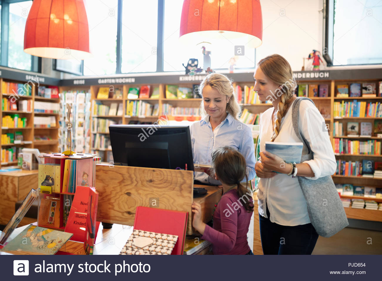 Bookstore worker helping mother and daughter at computer - Stock Image