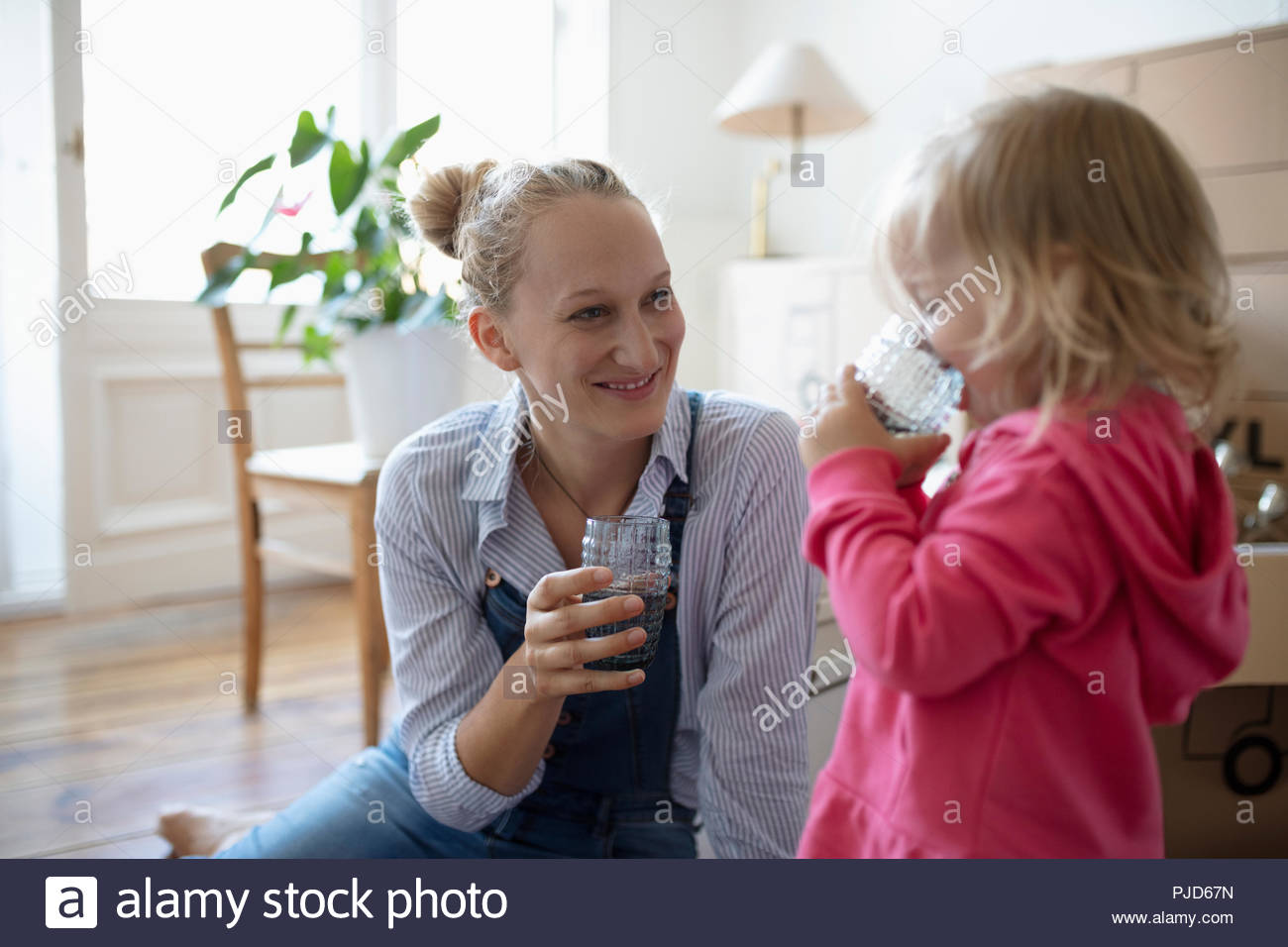 Mother and daughter drinking water, taking a break from moving in - Stock Image