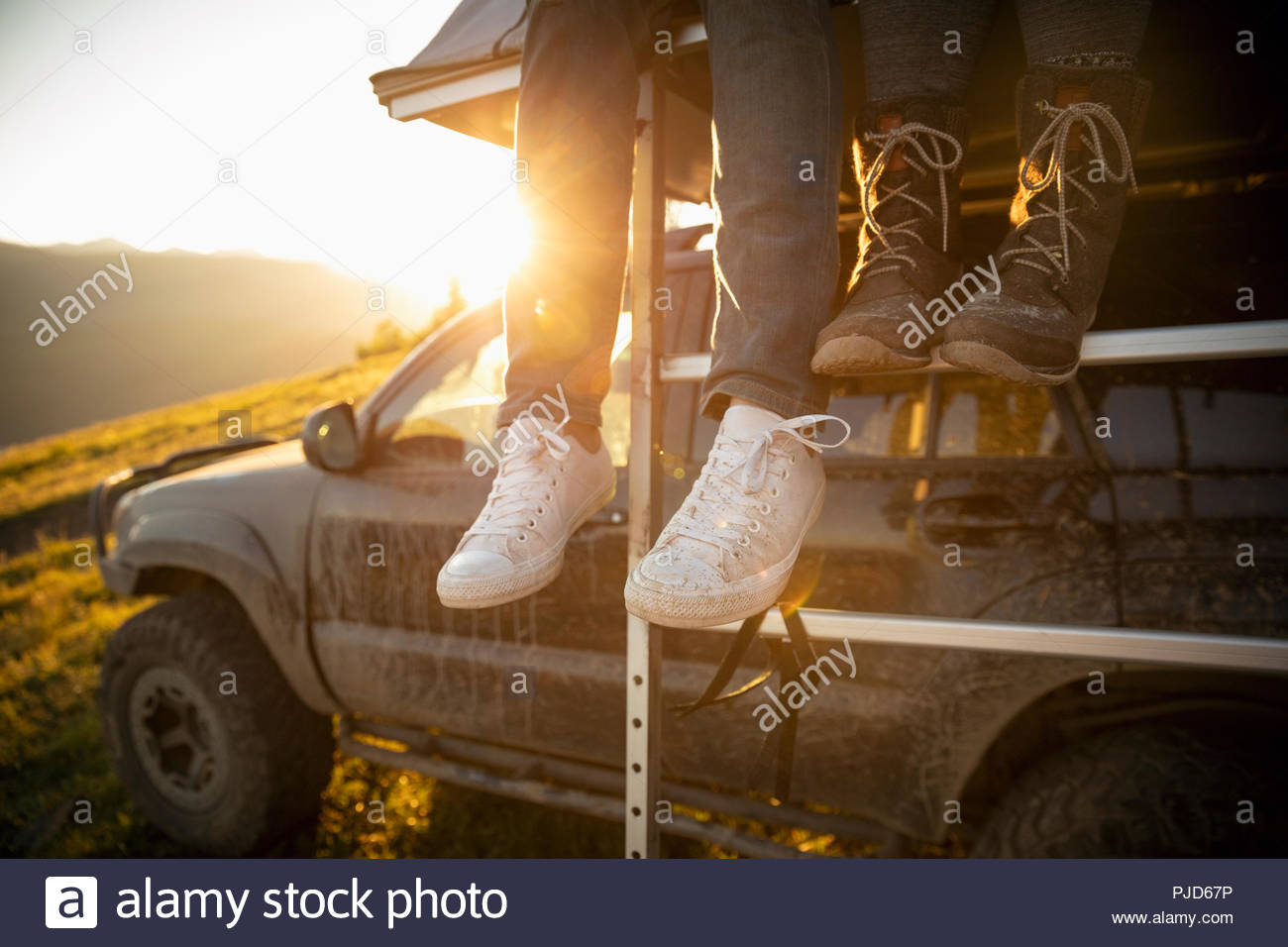 Couple dangling feet from SUV rooftop - Stock Image