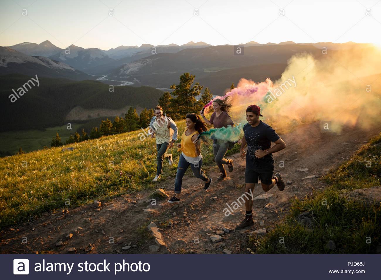 Playful friends enjoying colorful smoke bombs on sunny mountain road, Alberta, Canada - Stock Image