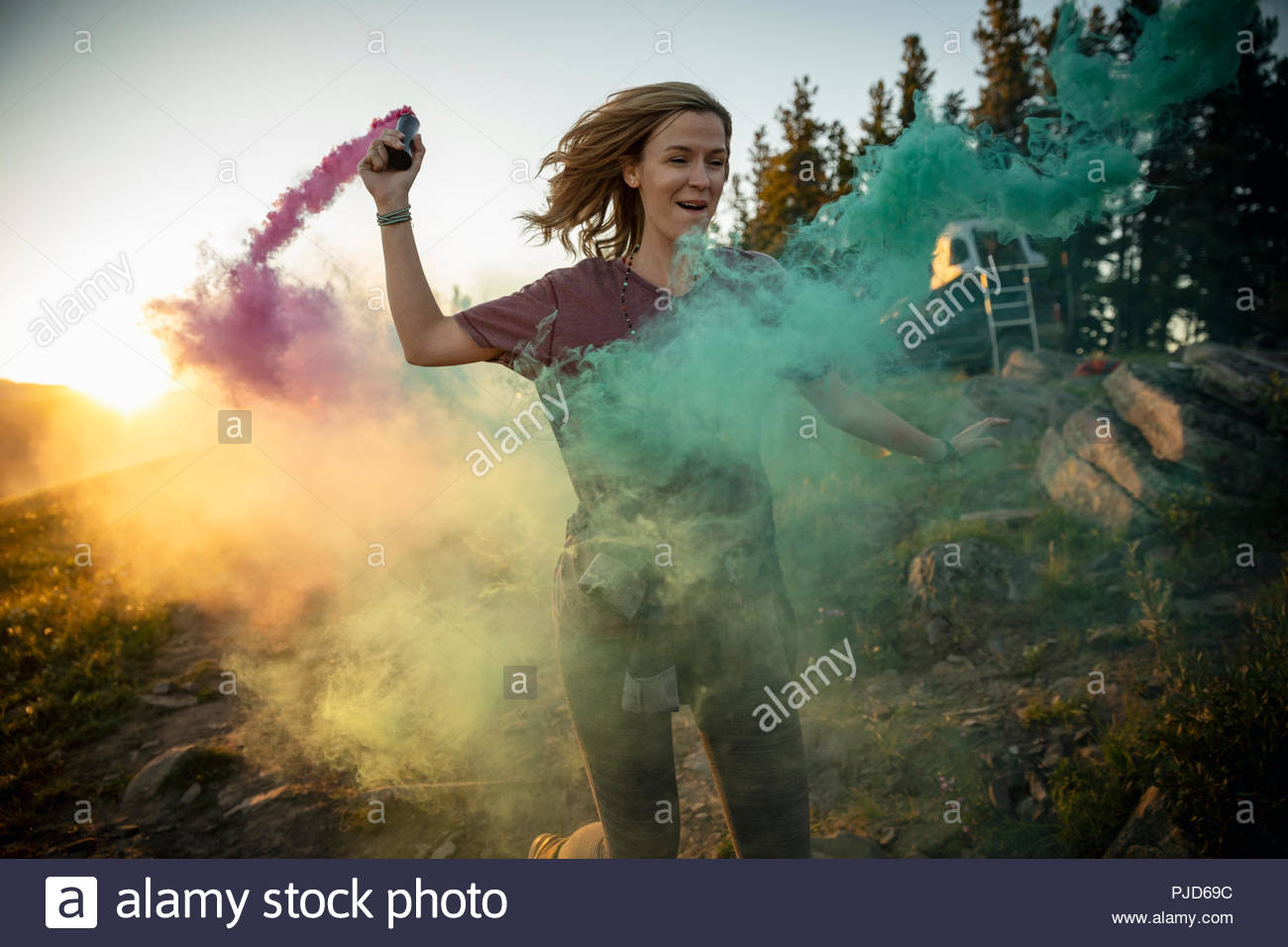 Playful woman running with colorful smoke bombs - Stock Image