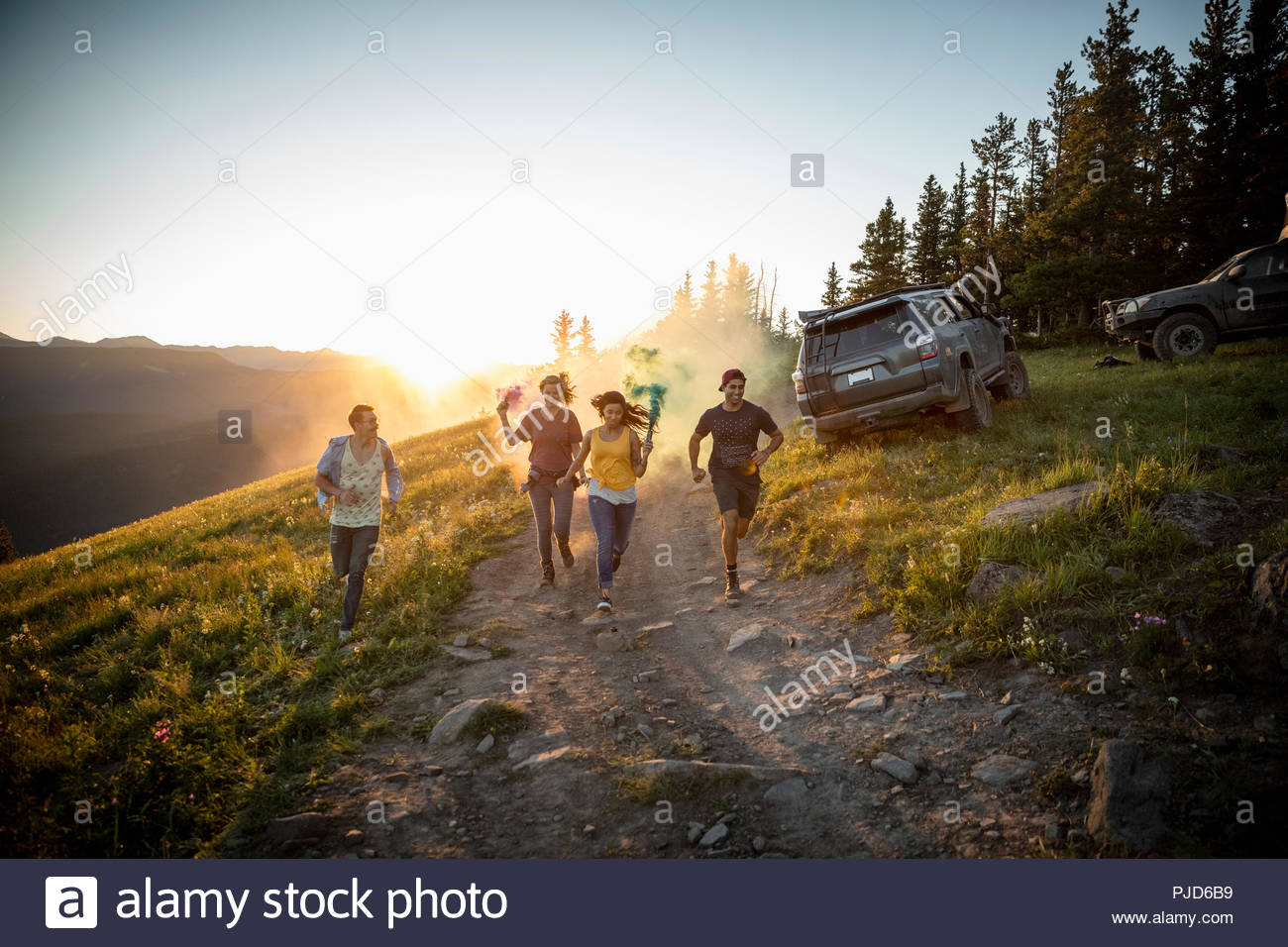 Playful friends running with smoke bombs on remote road, Alberta, Canada - Stock Image