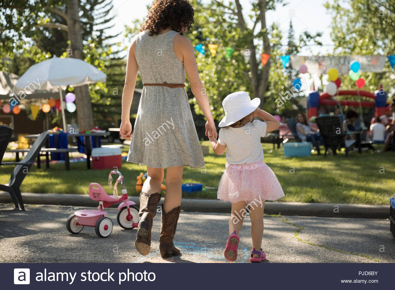 Mother and daughter walking toward summer neighborhood block party in park - Stock Image