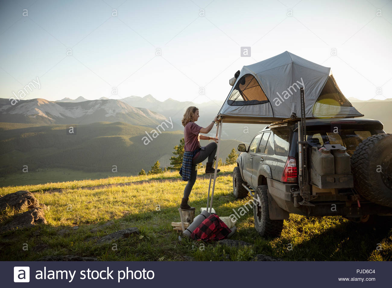 Woman camping, climbing up to SUV rooftop tent in idyllic mountain field, Alberta, Canada Stock Photo
