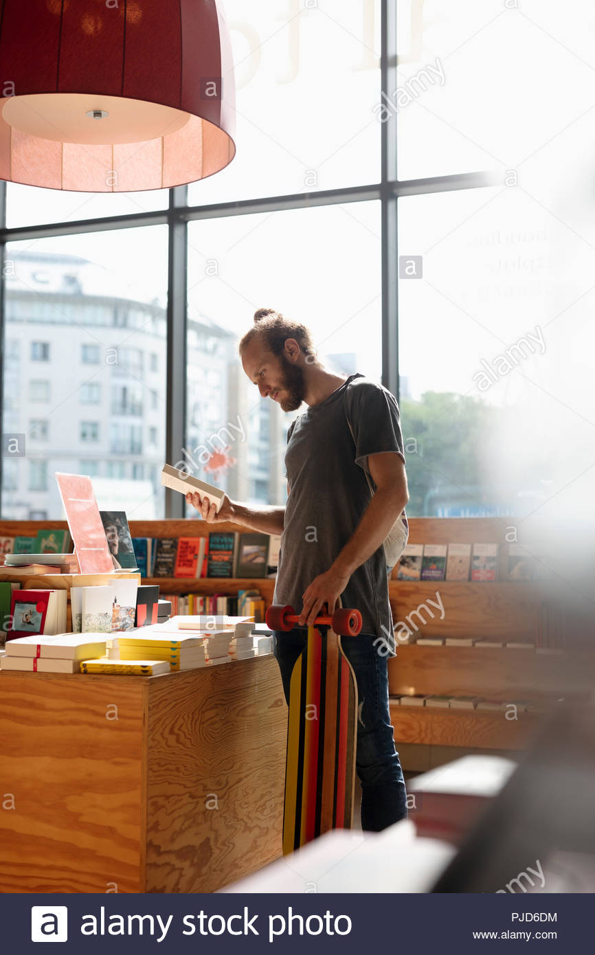 Man with skateboard shopping in bookstore - Stock Image