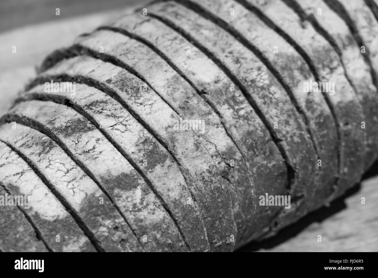 Sliced home baked artisan bread loaf, - abstract monochrome texture and pattern in black and white - Stock Image