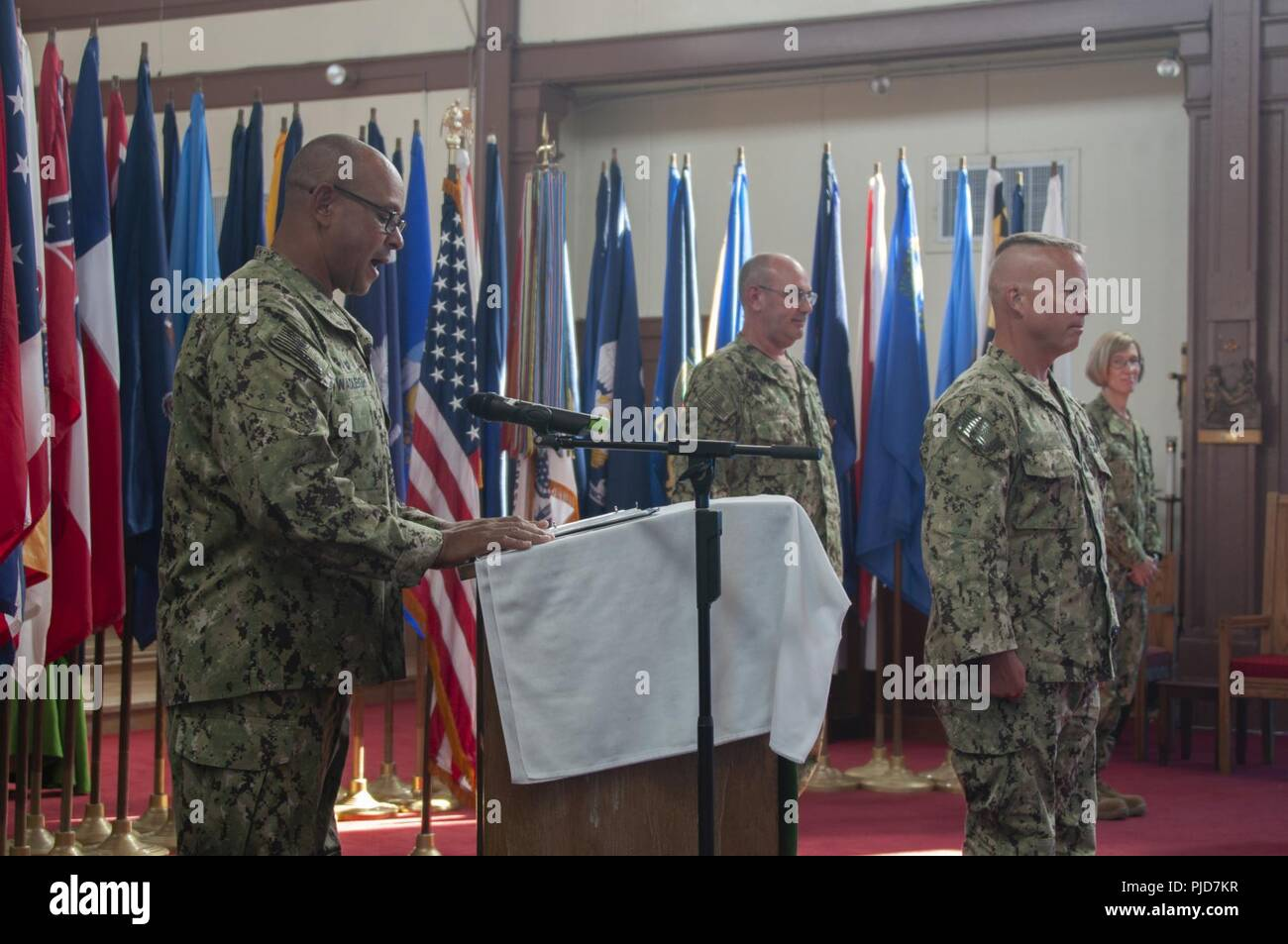 Captain Matthew Wadleigh, Commanding Officer of Port Security Unit 309 reads his orders during the Transfer of Authority ceremony held July 24, 2018. Rear Admiral Ring, commander, Joint Task Force Guantanamo presides over ceremony and joined with Commander Laila Grassley Commanding Officer of Port Security Unit 311.  Unlike a Change of Command a Transfer of Authority differs as the entire unit is relieved in lieu of only the commanding officer. U.S. Coast Guard Stock Photo