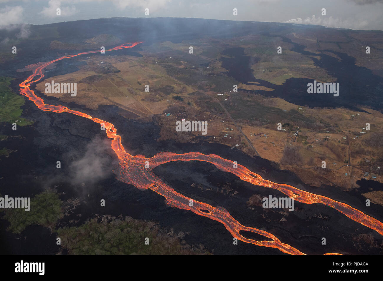river of lava drains from Kilauea Volcano east rift zone near Pahoa, Hawaii through Kapoho toward ocean entry at Ahalanui on the Big Island - Stock Image