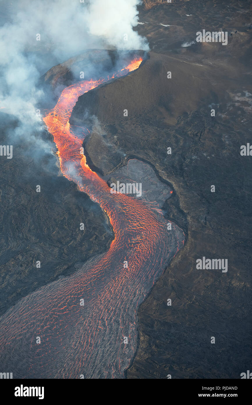 lava erupting from fissure 8 of the Kilauea Volcano east rift zone in Leilani Estates subdivision, near Pahoa, pours out of its cinder cone and flows  - Stock Image